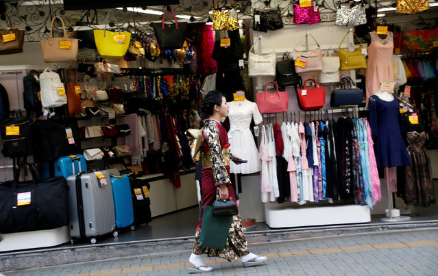 A woman in a kimono walks past a shop in a shopping district in Tokyo, Japan March 23, 2017. (Photo by Kim Kyung-Hoon/Reuters)