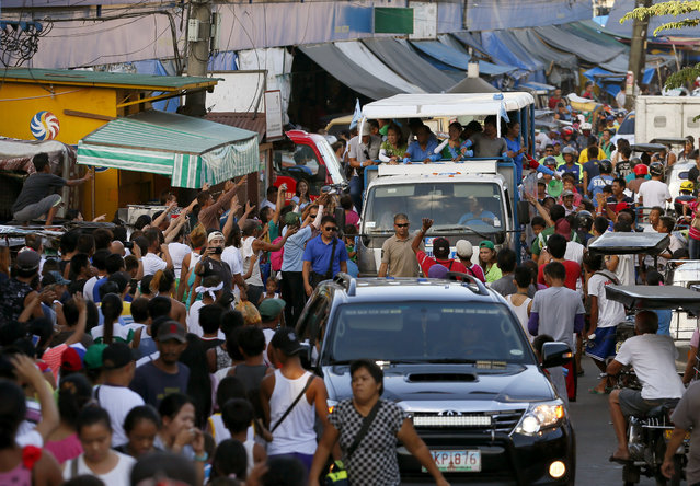 The campaign sortie of Presidential candidate Vice-president Jejomar Binay and Congressman Manny Pacquiao, who is running for senator in Monday's national elections, passes thru narrow streets in Navotas north of Manila, Philippines Friday, May 6, 2016. Binay is running fourth in the latest poll survey while Pacquiao is in the top five of the possible senators. The country will hold a national election on Monday to succeed President Benigno Aquino III with tough-talking Mayor Rodrigo Duterte leading among five presidential candidates in most surveys. (Photo by Bullit Marquez/AP Photo)