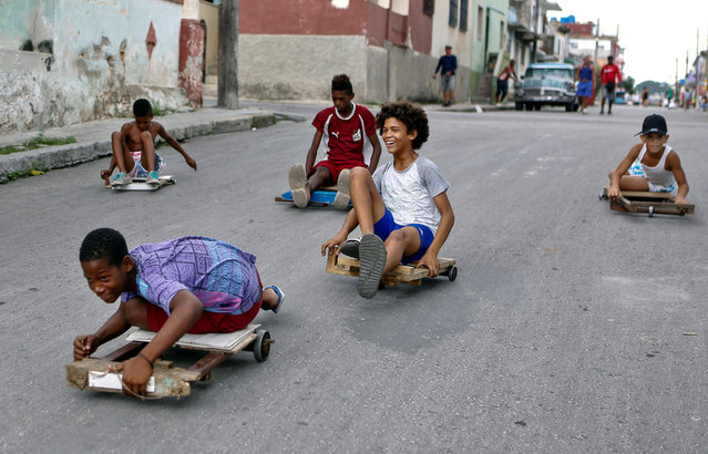 """Children play with their """"chivichanas"""", hand-made trolleys they races with, at a street of Havana, Cuba, 19 June 2019. Children in Havana are on school holidays. (Photo by Yander Zamora/EPA/EFE)"""