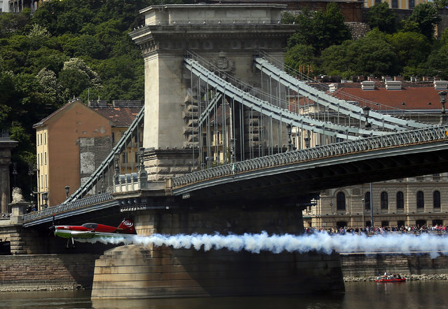 Zoltan Veres of Hungary flies with his MXS airplane under Budapest's Chain Bridge during an air show, May 1, 2014. (Photo by Laszlo Balogh/Reuters)