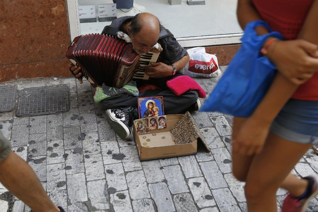 A woman passes by a street musician sit on the ground and plays with his accordion at a main shopping pedestrian street in central  Athens, Friday, July 10, 2015. Greece's Prime Minister Alexis Tsipras will seek backing for a harsh new austerity package from his party Friday to keep his country in the euro. (Photo by Petros Karadjias/AP Photo)