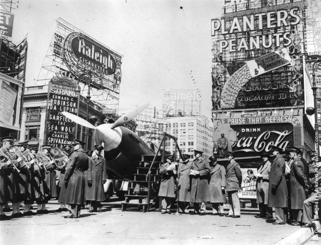 1941: A military band and a Curtiss P-40 Army Pursuit plane in Duffy Square on the corner of Times Square in New York. The plane is part of an exhibition to encourage men to join the Army Air Corps