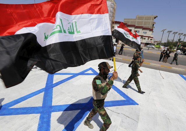Iraqi Shiite Muslim men from Hashid Shaabi (Popular Mobilization) march along a street painted with the Israeli flag while as they hold an Iraqi flag during a parade marking the annual al-Quds Day, or Jerusalem Day, on the last Friday of the Muslim holy month of Ramadan in Baghdad, July 10, 2015. (Photo by Thaier al-Sudani/Reuters)