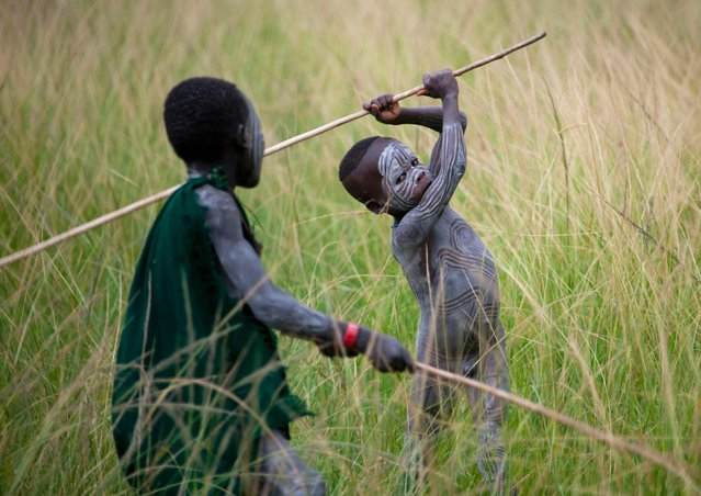 Children of a very young age are seen copying the warriors in dress and wielding the stick weapons. (Photo by Eric Lafforgue/Exclusivepix Media)