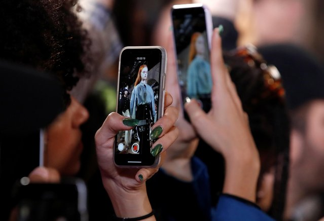A guest takes pictures with her mobile phones as a model presents a creation by designers Victoria Feldman and Tomas Berzins as part of their Spring/Summer 2020 women's ready-to-wear collection show for Victoria/Tomas during Paris Fashion Week in Paris, France, September 24, 2019. (Photo by Gonzalo Fuentes/Reuters)