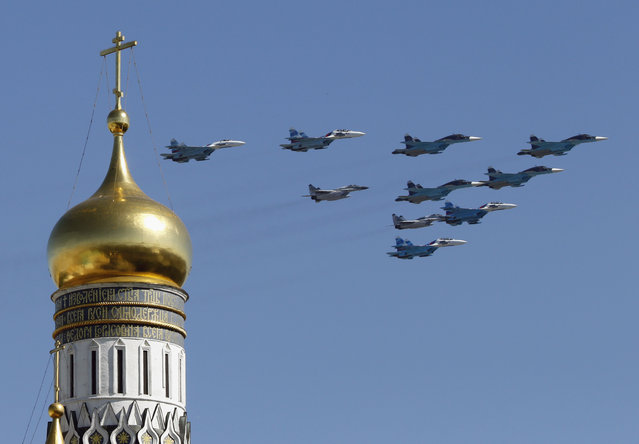 Russian military planes fly above the Kremlin, with the Ivan the Great Bell Tower seen in the foreground, during the Victory Day parade in Moscow's Red Square May 9, 2014. Russian President Vladimir Putin praised the Soviet role in defeating fascism on Friday, the anniversary of the World War Two victory over Nazi Germany, and said those who defeated fascism must never be betrayed. (Photo by Tatyana Makeyeva/Reuters)