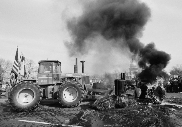 A tractor with front and blade pushes the burning hulk of another tractor out of the Washington on Tuesday, February 6, 1979 in to clear the way for a tractorcade from the Mall area to the White House. The farmers set fire to the tractor earlier in the day when they were prevented from leaving the Mall area. (Photo by AP Photo)