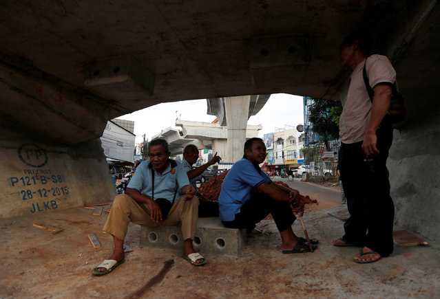 Public transport drivers chat as they wait for passengers as they sit inside precast concrete for a flyover construction in Jakarta, Indonesia, May 11, 2016. (Photo by Reuters/Beawiharta)