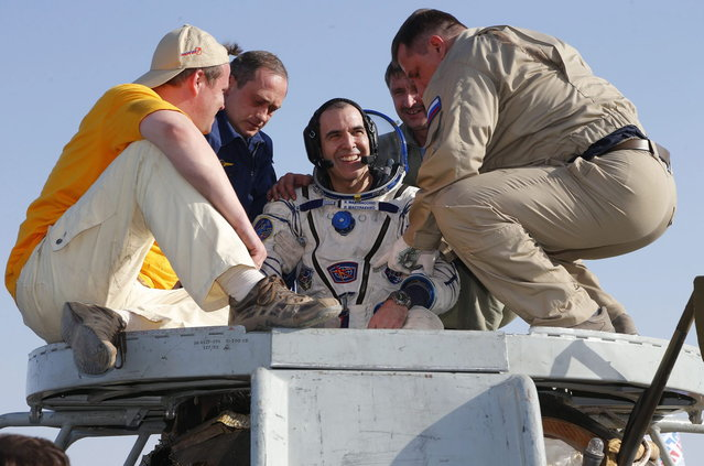 Russian space agency rescue team help U.S. astronaut Rick Mastracchio to get off the capsule of the Russian Soyuz TMA-11 module shortly after the landing, about 150 kilometers (93 miles) southeast of the Kazakh town of Dzhezkazgan, Kazakhstan, Wednesday, May 14, 2014. The Soyuz space capsule carrying three astronauts who had spent a half-year aboard the International Space Station landed Wednesday in the steppes of Kazakhstan. (Photo by Dmitry Lovetsky/AP Photo)
