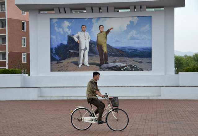 A local resident cycles past a mural depicting former North Korean leaders Kim Il Sung and Kim Jong Il in the North Korean port of Rajin July 18, 2014. (Photo by Yuri Maltsev/Reuters)
