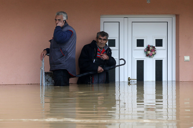 Two men stand in the waters in front of their flooded house as they wait to be evacuated in the town of Obrenovac, east from Belgrade May 16, 2014. The heaviest rains and floods in 120 years have hit Bosnia and Serbia, killing five people, forcing hundreds out of their homes and cutting off entire towns. (Photo by Marko Djurica/Reuters)