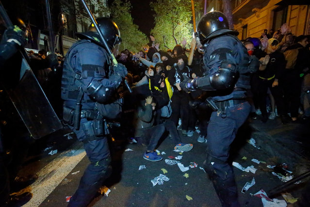 """Protesters clash with Catalan regional police """"Mossos D'Esquadra"""" officers during a protest in front of the Spanish Government delegations in Barcelona on October 15, 2019, as Catalonia geared up for more upheaval a day after thousands of pro-independence activists stormed Barcelona airport in an angry response to Spain's jailing of nine of its leaders following a failed secession bid. (Photo by Pau Barrena/AFP Photo)"""