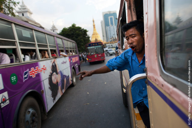 A Burmese man working on a city bus calls out for passengers to board at a bus stop in Yangon, Myanmar