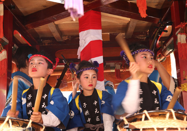 Japanese children dressed in traditional festival costumes as perform Taiko drum on the huge paper doll cart of historical figure during the Mikuini annual festival on May 20, 2014 in Sakai, Japan. The annual festival takes place from May 19-21 and is attended by thousands of visitors. During the festival people dressed in traditional Japanese costumes pull carts carrying 6 meter high dolls of Japanese historical figures through the narrow streets. The origins of the festival are unclear but its history can be traced back more than 250 years. (Photo by Buddhika Weerasinghe/Getty Images)