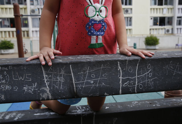 In this Tuesday, July 7, 2015 photo, a girl climbs on a bar marked with noughts and crosses (tic-tac-toe) at a park in Hong Kong. (Photo by Kin Cheung/AP Photo)