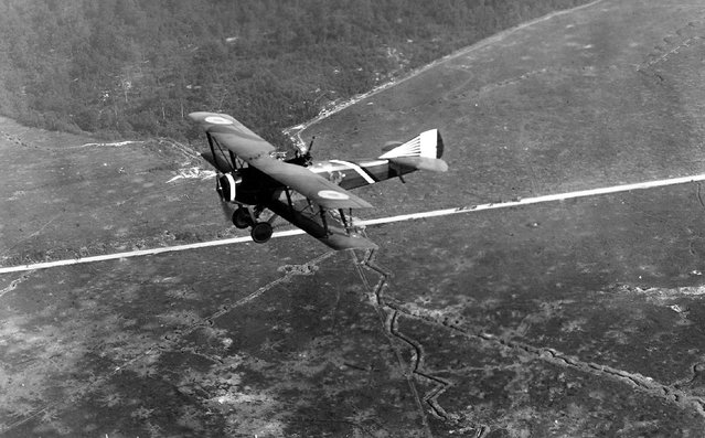 A French SPAD S.XVI two-seat biplane reconnaissance aircraft, flying over Compeign Sector, France ca. 1918. Note the zig-zag patterns of defensive trenches in the fields below. (Photo by San Diego Air and Space Museum Archive via The Atlantic)