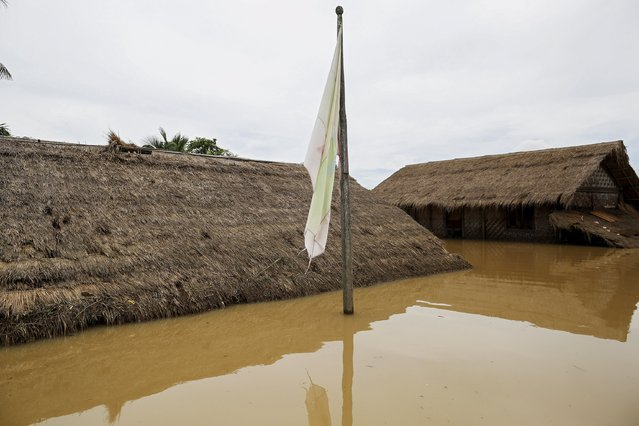 The Myanmar national flag is seen in a flooded village at Kawlin township, Sagaing division, Myanmar, July 21, 2015. (Photo by Soe Zeya Tun/Reuters)