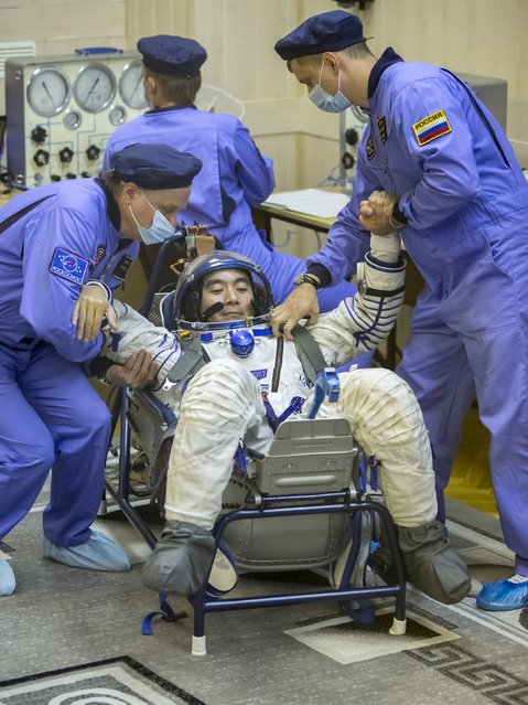 Kimiya Yui of Japan, a member of the International Space Station crew, is assisted during a space suit check at the Baikonur cosmodrome, Kazakhstan, July 22, 2015. (Photo by Shamil Zhumatov/Reuters)