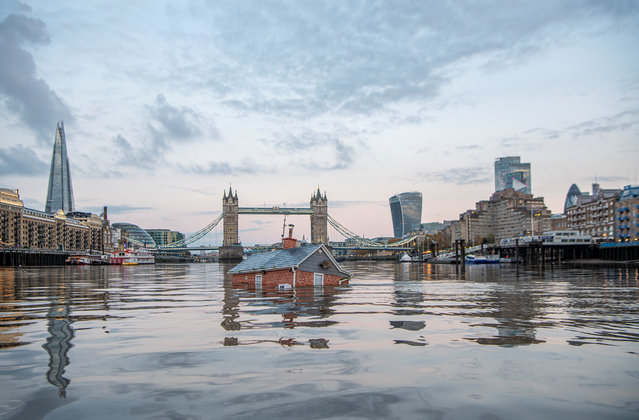 A mock-up of a typical British suburban home is seen sinking into the River Thames, in a protest by Extinction Rebellion to demand faster government action on climate change in London, Britain on November 10, 2019. (Photo by Extinction Rebellion/Handout via Reuters)