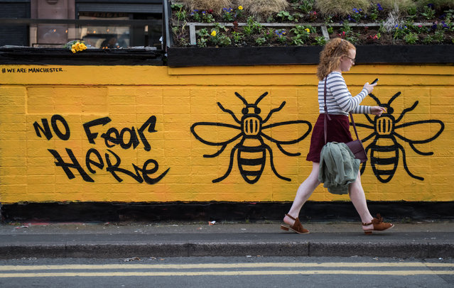 A woman passes a street-art graffiti mural, created following the May 22 terror attack at the Manchester Arena, featuring bees, which are synonymous with Manchester as a symbol of the city's industrial heritage, in Stevenson Square, Manchester, northwest England on May 25, 2017. Britain Thursday closed in on a jihadist network thought to be behind the May 22, 2017 Ariana Grande concert attack, as grief mixed with anger at the US over leaked material from the probe. Britain has raised its terror alert to the maximum level and ordered troops to protect strategic sites after 22 people were killed in a suicide bomb attack on a Manchester pop concert. (Photo by AFP Photo)