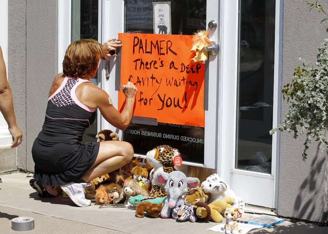A woman writes on a sign outside Dr. Walter James Palmer's dental office in Bloomington, Minn., Wednesday, July 29, 2015. (Photo by Ann Heisenfelt/AP Photo)