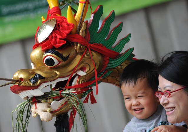 A boy is held next to a dragon head adorning a boat during the dragon boat racing in the Aberdeen typhoon shelter in Hong Kong on June 23, 2012. According to legend national hero Qu Yuan died fighting for political reform. Townspeople tried to rescue him from drowning in the river and beat drums to scare the fish and now the tradition is continued with Dragon Boat races. (Photo by Antony Dickson/AFP Photo)