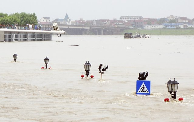 A traffic sign and the tips of street lamps are seen among floodwaters as a riverside street is submerged by an overflowing river after heavy rainfalls hit Lanxi, Zhejiang province June 22, 2014. Severe rainstorms in southern China have left at least 26 dead and three others missing. The Ministry of Civil Affairs says 4.9 million people have been affected, Xinhua News Agency reported. (Photo by Reuters/Stringer)