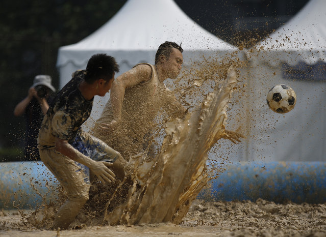 Players battle for the ball during their match at the swamp soccer China tournament in Beijing, June 26, 2014. The 32 teams from across the country participated in the soccer event to celebrate the 2014 World Cup in Brazil. (Photo by Kim Kyung-Hoon/Reuters)