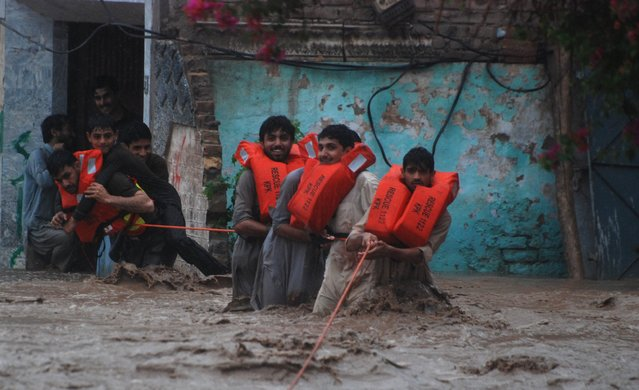 Rescue workers help stranded residents after heavy rainfall caused flooding in Peshawar, Pakistan, July 26, 2015. Flash flooding caused by torrential monsoon rains has killed at least 28 in Pakistan and affected hundreds of thousands of people, according to aid agencies, with further downpours expected in the coming days. (Photo by Khuram Parvez/Reuters)