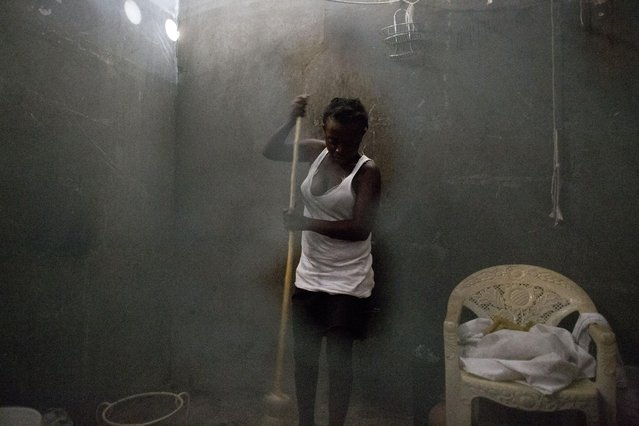 In this June 27, 2015 photo, Neslie Etienne, 28, seen through a hole in mosquito netting, sweeps the room she shares with her husband and six-year-old son in an abandoned shipping container in Port-au-Prince, Haiti. Forced evictions and rental subsidies cleared many of the camps that had been set up for those displaced by the 2010 earthquake, but didn't provide long-term solutions for those left homeless by the quake. (Photo by Rebecca Blackwell/AP Photo)
