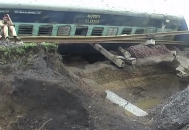 In this image made from video, a man sits alongside a derailed train in Harda in Madhya Pradesh state, India, Wednesday, August 5, 2015. (Photo via AP Video)