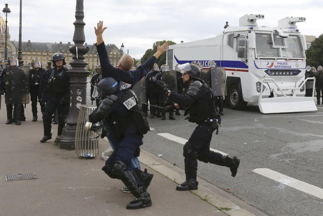 French CRS riot police apprehend a demonstrator during clashesat the Invalides square during a demonstration in Paris as part of nationwide protests against plans to reform French labour laws, France, June 14, 2016. (Photo by Jacky Naegelen/Reuters)