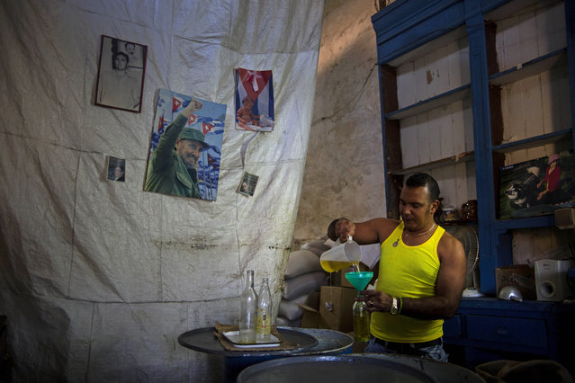 A worker pours cooking oil into a bottle for a waiting customer in a state bodega decorated with images of Fidel and Raul Castro in Old Havana, Cuba, Tuesday, Feb. 17, 2015. (Photo by Ramon Espinosa/AP Photo)