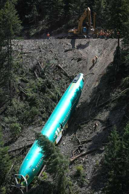 Work crews remove one of the Boeing 737 fuselages that plunged into the Clark Fork River east of Superior, Mont., on Monday, July 7, 2014. Boeing is deciding what to do with six new commercial airplane bodies that fell off a train in western Montana, including three that slid down a steep riverbank, a company spokeswoman said Monday. (Photo by Joshua Trujillo/AP Photo)