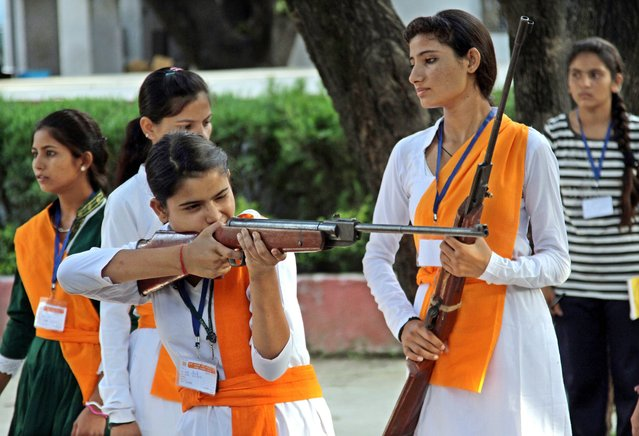 Indian girls of Durga Vahini, a Hindu hardliner women's organization take part in week-long self defense training camp in Jammu, the winter capital of Kashmir, India, 07 July 2014. In the wake of the increase in crime against women in the country these young girls are being given training to operate sticks and guns and to develop the skills of self defense. (Photo by Jaipal Singh/EPA)