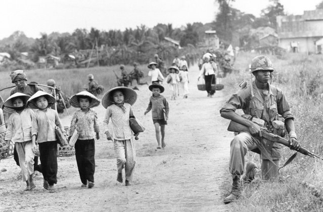 In this December 1965 file photo shot by Associated Press photographer Horst Faas, a U.S. 1st Division soldier guards Route 7 as Vietnamese women and school children return home to the village of Xuan Dien from Ben Cat, Vietnam