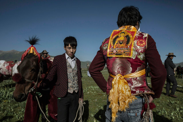 An ethnic Tibetan nomad wears a picture of the Buddhs on his back before racing his horse at a local government sponsored festival on July 26, 2015 on the Tibetan Plateau in Yushu County, Qinghai, China. (Photo by Kevin Frayer/Getty Images)