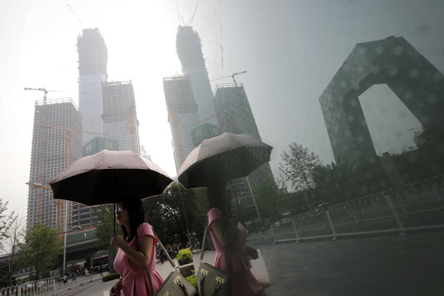 A woman carries an umbrella past a shopping mall's window with reflection of construction buildings at the Central Business District in Beijing, Monday, July 17, 2017. (Photo by Andy Wong/AP Photo)