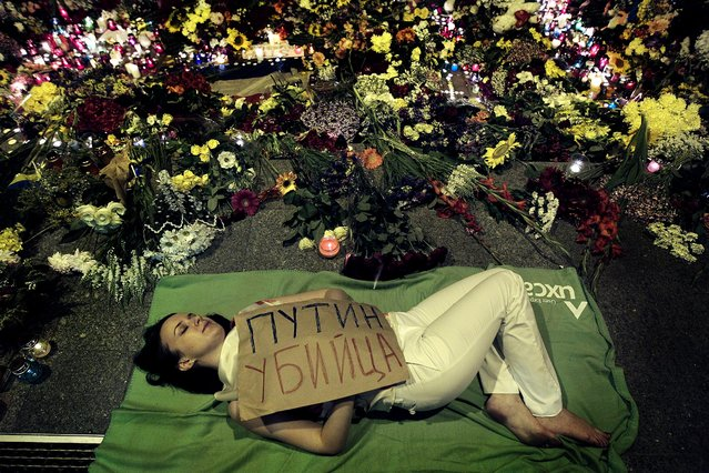 """A Ukrainian woman lies down in front of the Dutch embassy in Kiev, holding a poster reading """"Putin is a killer"""", on Jule 17, 2014. A Malaysian Airlines passenger jet was shot down in eastern Ukraine on Thursday, and both the Ukrainian government and pro-Russian rebels blamed one another for the attack. (Photo by Sergei Chuzavkov/Associated Press)"""