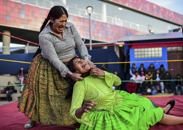 """Bolivian wrestler Ana Luisa Yujra (L), aka """"Jhenifer Two Faces"""" and Lidia Flores, aka """"Dina, The Queen of the Ring"""", both members of the Fighting Cholitas, fight at Sharks of the Ring wrestling club in El Alto, Bolivia, on November 24, 2019. After a fortnight hiatus due to anti-government protests and blockades, the Fighting Cholitas are back in the ring. The unrest was triggered by the disputed October 20 election, which Evo Morales claimed to have won and opposition groups said was rigged. (Photo by Ronaldo Schemidt/AFP Photo)"""