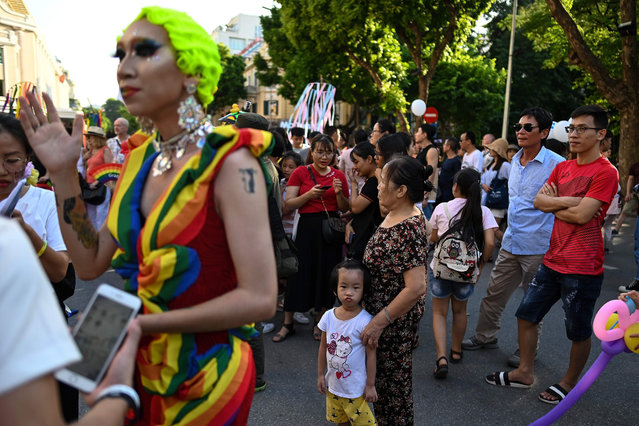 Vietnamese men (R) look on as participants take part in the annual Hanoi Pride 2019 parade, which champions LGBT rights in the country, in Hanoi on September 22, 2019. (Photo by Manan Vatsyayana/AFP Photo)