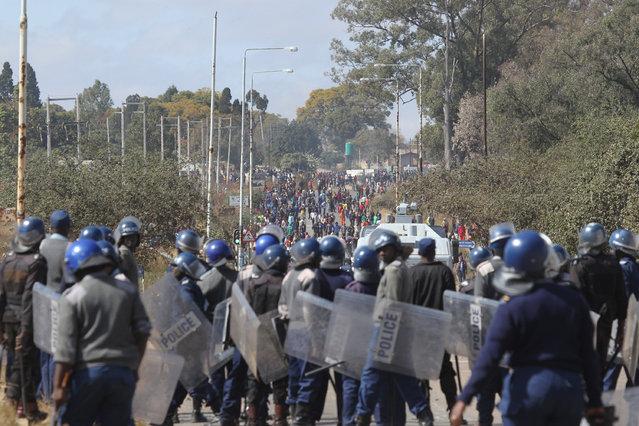 Armed Zimbabwean police clash with rioters in Harare, Monday, July, 4, 2016. (Photo by Tsvangirayi Mukwazhi/AP Photo)