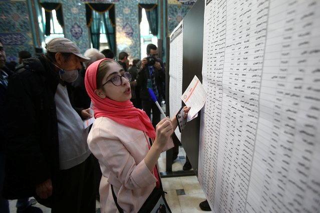 A woman selects her candidates during parliamentary elections at a polling station in Tehran, Iran on February 21, 2020. (Photo by Nazanin Tabatabaee/WANA (West Asia News Agency) via Reuters)