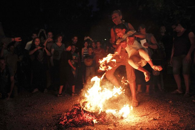 A woman helps a girl cross a fire as part of a traditional custom during the annual Klidonas event that takes place on the eve of the feast of Saint John the Baptist, in Athens June 23, 2014. (Photo by Alkis Konstantinidis/Reuters)
