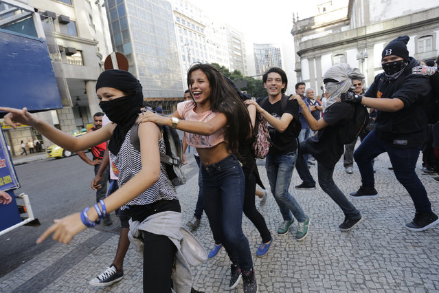 Students shout slogans during a protest demanding better education and protesting the money spent on the Olympics, in Rio de Janeiro, Brazil, Wednesday, July 6, 2016. With the Olympics set to start on August 5, the games and the city have been overshadowed by security threats, violence, the Zika virus and a national political corruption scandal. (Photo by Silvia Izquierdo/AP Photo)