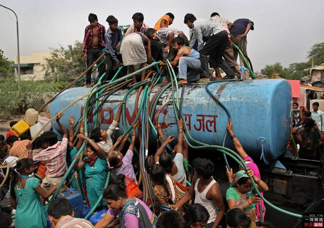 Residents crowd a government tanker delivering drinking water in New Delhi, India, on July 6, 2012. A patchy monsoon season has left many residents scrambling for water. (Photo by Kevin Frayer/AP)