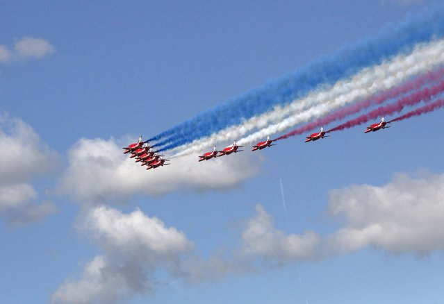 The Red Arrows display team perform a fly past to officially open the 2014 Farnborough International Airshow in Farnborough, southern England July 14, 2014. (Photo by Kieran Doherty/Reuters)