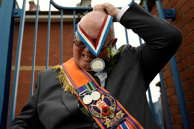 A member of the Twelfth of July Orange Order parade is seen putting on a medal during a march through Crumlin Road in Belfast, Northern Ireland, July 12, 2016. (Photo by Clodagh Kilcoyne/Reuters)