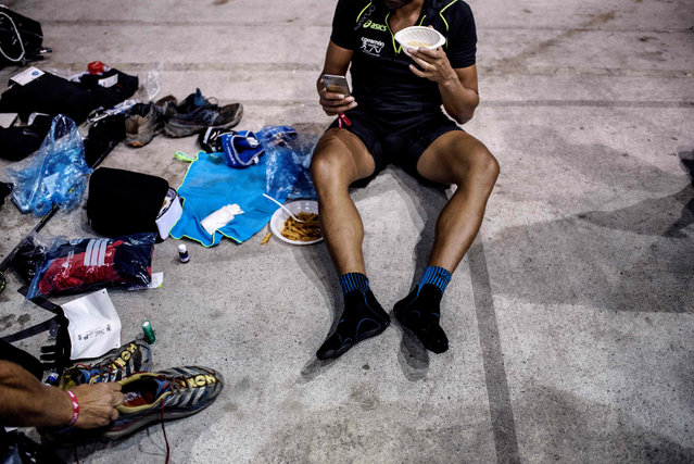 An Ultra- trailer eats and rests at a refreshment post on September 2, 2017 in Courmayeur, Italy, during the 15 th edition of the Mount Blanc Ultra Trail (UTMB), a 170 km race around the Mont Blanc crossing France, Italy and Switzerland. (Photo by Jeff Pachoud/AFP Photo)