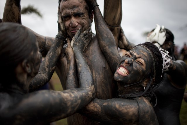 Women put mud over a man at a mud party during Carnival celebrations in Paraty,  Brazil, Saturday, March 5,  2011. (Photo by Rodrigo Abd/AP Photo)